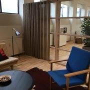 Venterum indrettet som stue med polstrede møbler, gulvtæppe og gardiner - porøse overflader som lyddæmper
